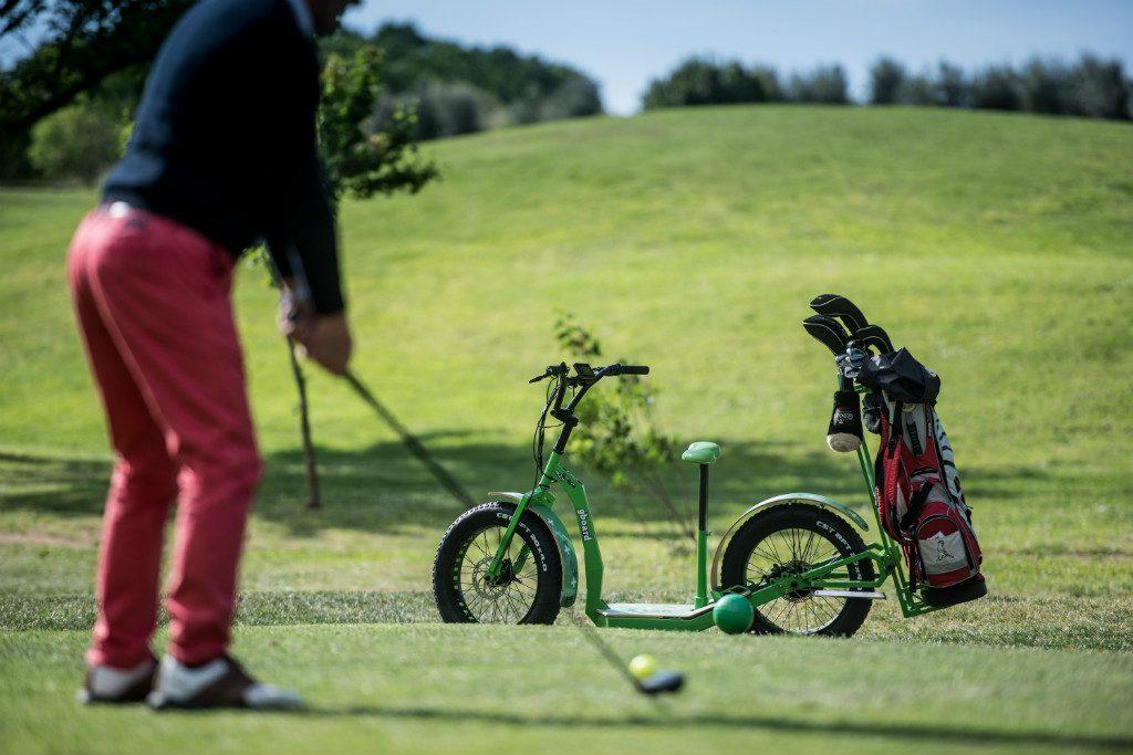 golfista che sta colpendo una pallina e sullo sfondo un greenboard golf edition verde con portasacca